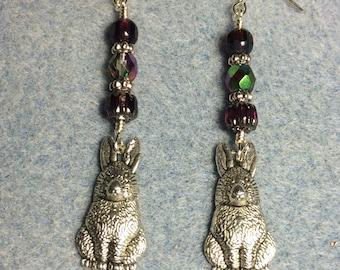 Large rabbit charm dangle earrings adorned with dark purple Czech glass beads.