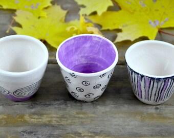Three decorated ceramic cups set