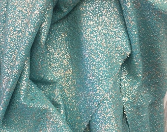 100% Polyester 4 way stretch fabric with glued silver glitter. 60 inches wide. Teal color.