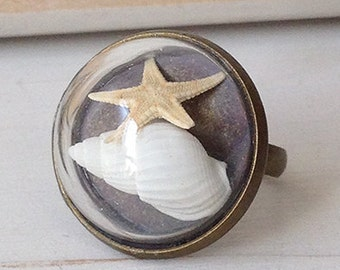 Ring with glass sphere and shell