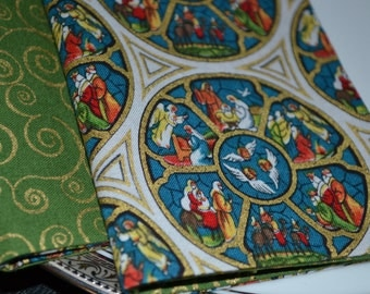 Set of 8 reversible cloth napkins featuring stained glass images of the Christmas story.