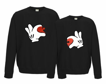 His and her's matching sweatshirts with hands holding half heart.