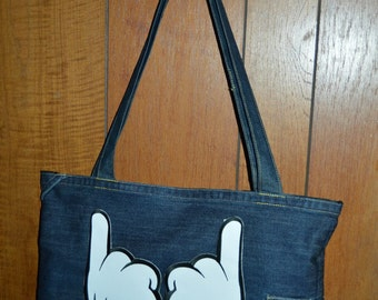 bag has hands in jeans with 2 fingers embroidery has the machine