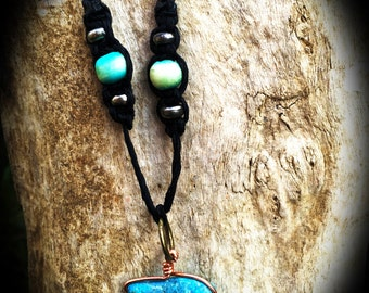 Turquoise stone with copper wrap on a hemp cord with wooden beads.