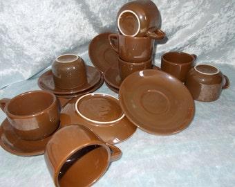 Set of eight brown metallic cups and saucers made of ceramics.