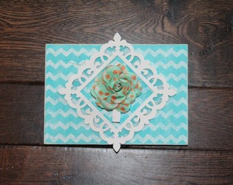 Painted teal with white chevron stripes wooden sign with a white frame and clothes pin in the middle with a flower on it