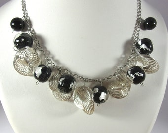 Black and silvery necklace with silvery spirals and black- silvery pearls .