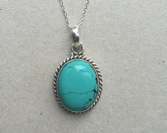 silver pendant inlayed with turquoise