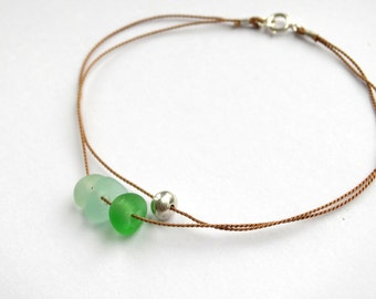 Silver pebble and sea glass bracelet. Fine silver pebble with genuine sea glass beads, on fine silk cord. Minimalist