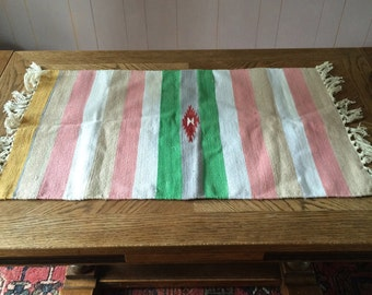 vintage, southwestern style rug, pink and green, with fringe, stripped
