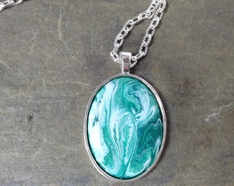A teal and white swirl enamel pendant necklace