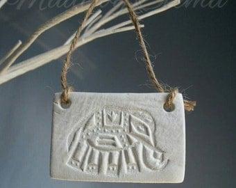 Little rectangular hanging clay plaque with ethnic elephant design. White clay with handstamped design. Natural twine to hang.