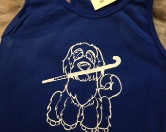 Bearded collie with hockey stick.