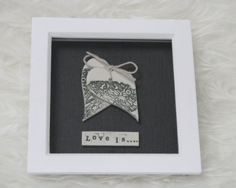 Ceramic hearts in box frame with 'Love is...' saying