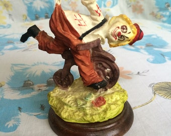 Vintage clown figure riding small bike - mounted on wooden base