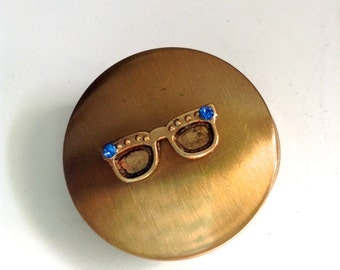 Cool Brass pill box.  Decorated with tiny Eye glasses with 2 Sapphire Rhinestones.  Vintage 1950.  Great gift.