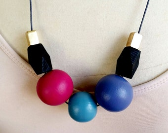 Wooden bead necklace. Features extra large 28mm beads. wood and metal. fuscia and purple.