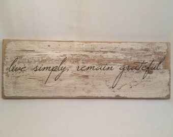 Wooden rustic quote sign. Live simply, remain grateful.