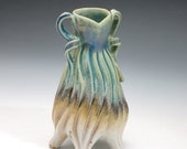 Porcelain lady vase in purple, turquoise, tan & white with grooves and handles, green blue
