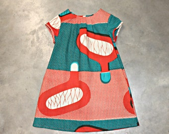 African print girls dress in a bold orange and teal geometric pattern