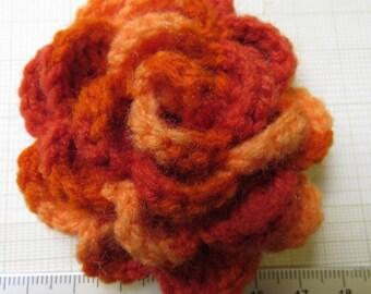 Irish crochet flower brooch in variegated orange wool