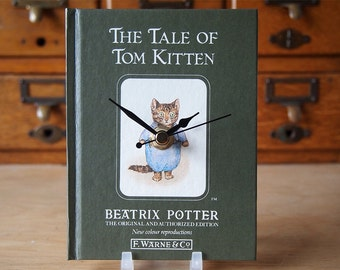 Cat clock made using an original book The Tale of Tom Kitten.  This Beatrix Potter favourite can be wall hung or use the stand supplied.
