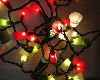 String of white lights wrapped in green, red and clear paper.