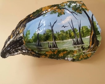 Oyster shell hand painted featuring a swamp scene.