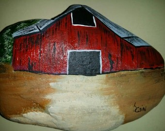 Hand painted rock featuring a red barn