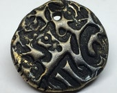Artisan designed textured polymer clay coin shaped disk with varied metallic finish