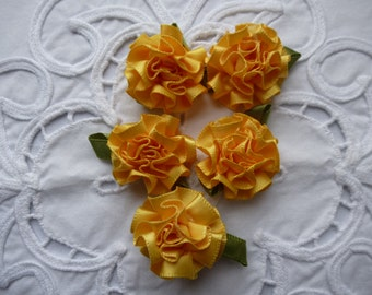 Yellow satin carnation flowers.   Approximately  25mm across.  Set of 12