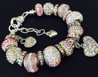 Pink and irredescent crystal charm bracelet with a dangling heart charm.