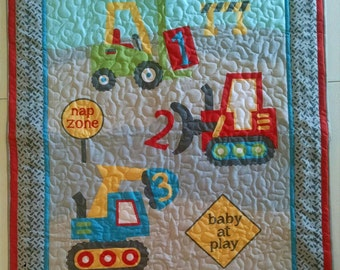 Adorable machine quilted toddler quilt made from material printed with construction trucks and signs