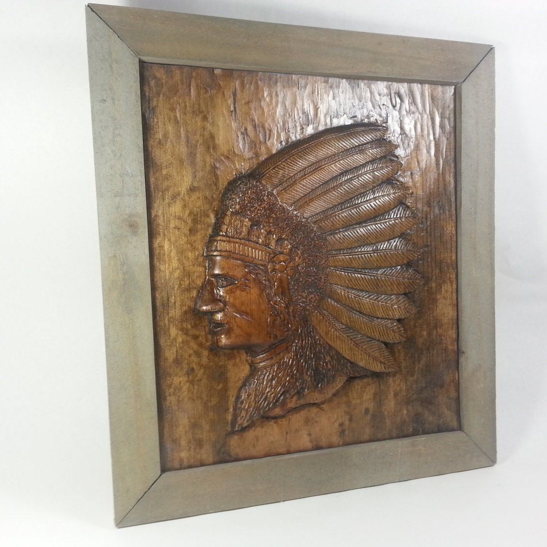 Relief carved indian in feather head dress from pine