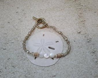 Gold bracelet with white shells