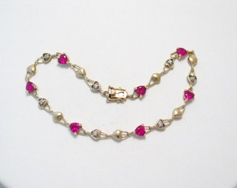 10k gold 7 1/4 inch wearing length bracelet ruby red heart gems accented w/ diamond chips padlock link pattern tennis style dainty feminine