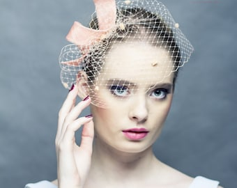 Modern curly wedding fascinator with delicate spotted veiling, sinamay bow headpiece, pink peach colour headpiece