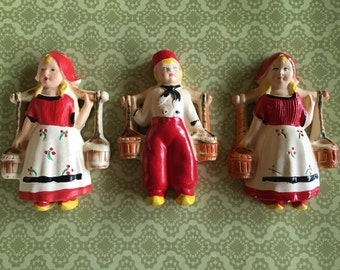 Trio of antique plaster chalkware Dutch boy and girls wall hangings