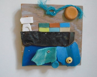 Cargoship. Artworks made of waste, plastic soup washed ashore. Wooden panel, size 15 x 15 cm.