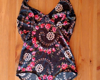Vintage woman swimsuit. Black swimsuit stamped red flowers.