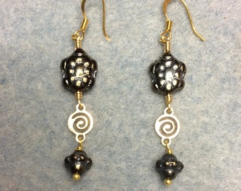 Metallic gray black turtle bead dangle earrings adorned with gold swirly connectors and metallic gray black Saturn beads.