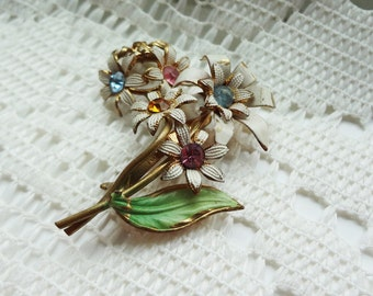 white and gold flower brooch with coloured rhinestones