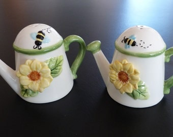 Pretty watering can salt and pepper shakers, decorated with flowers and bees.