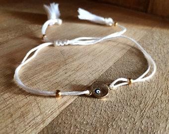 White string bracelet with beige tassels and evil eye breloque
