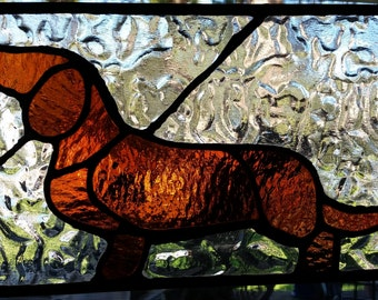 Brown dachshund on clear stained glass.