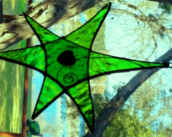 Green stained glass star / sun catcher with heart bead in center.