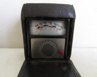 A Fixtus light meter/ flash in a leather case.