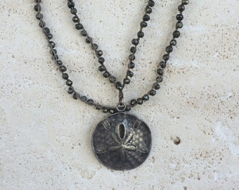 Metallic double strand necklace with sand dollar emblem
