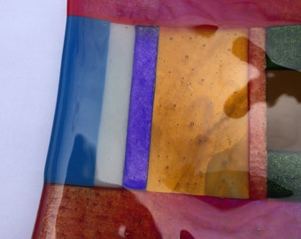Red iridescent fused glass bowl with multicoloured stripes