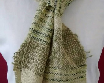 """Mixed fiber hand woven scarf in shades of green. Yarns include rayon, cotton and acrylic fibers. Size is 5"""" x 65"""", excluding fringe (3"""")."""